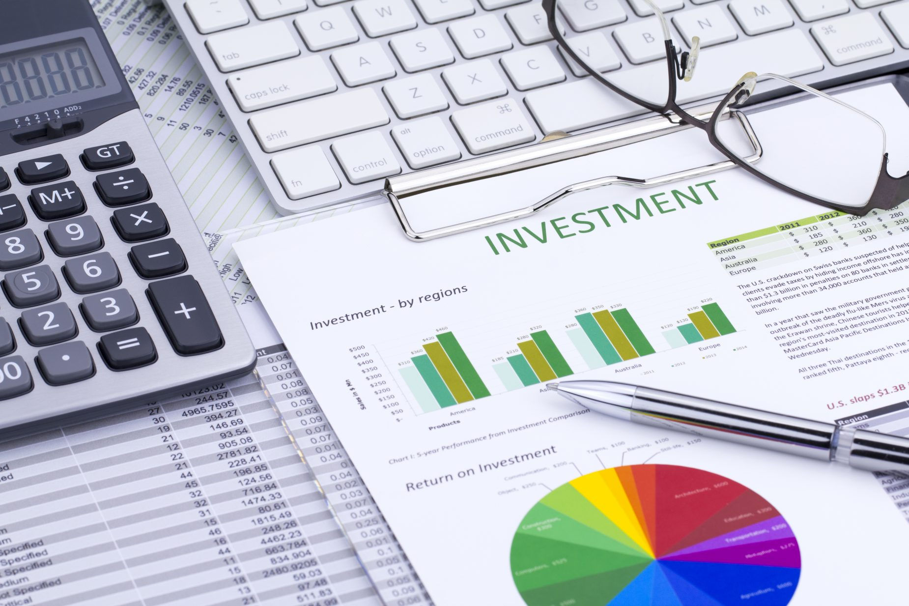 Investment analysis papers with calculator, keyboard and glasses